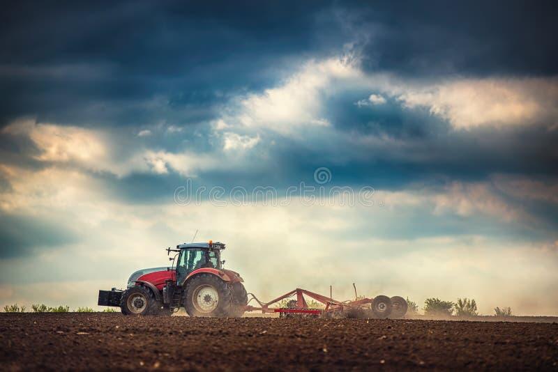 准备有温床耕地机的拖拉机的农夫土地 图库摄影