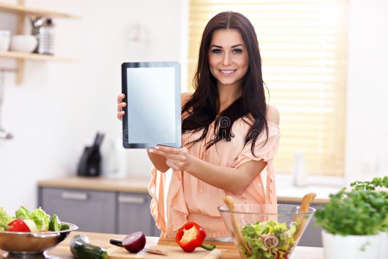 准备沙拉在现代厨房里和拿着片剂的愉快的妇女 免版税库存图片