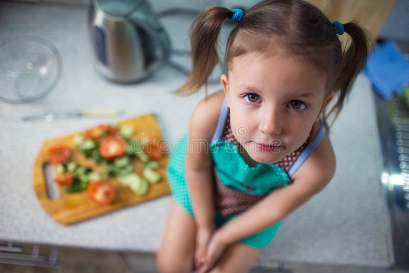 准备沙拉的小女孩在厨房里 库存照片