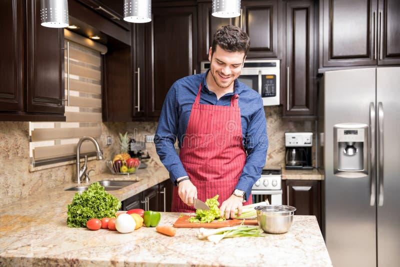 准备沙拉的年轻人在厨房里 库存照片