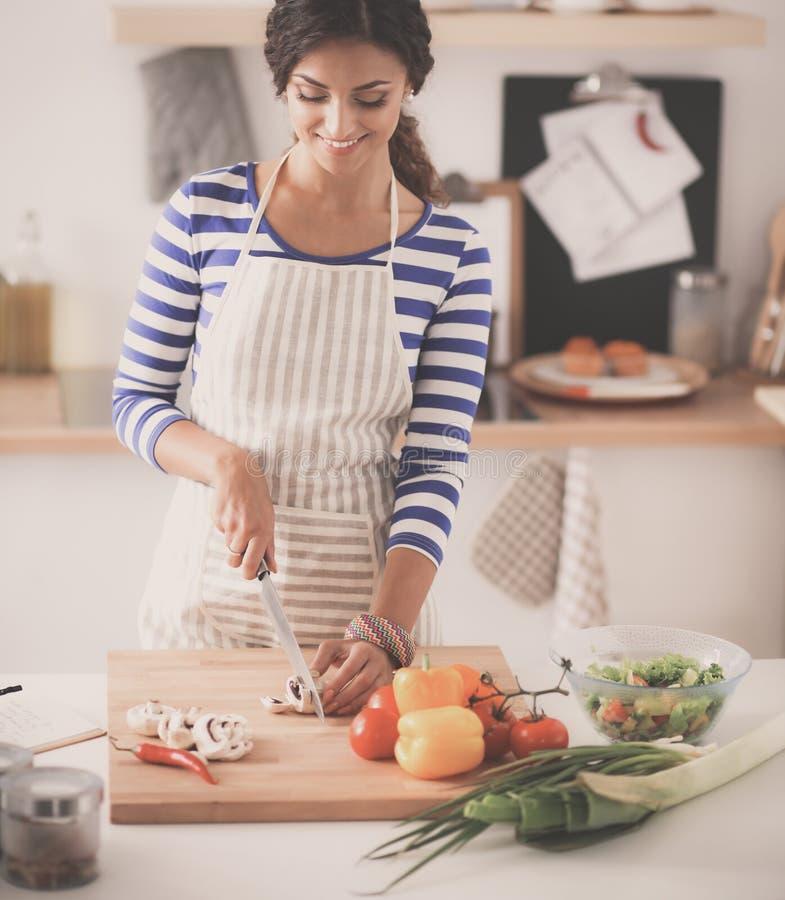 准备沙拉的微笑的妇女在厨房里 图库摄影