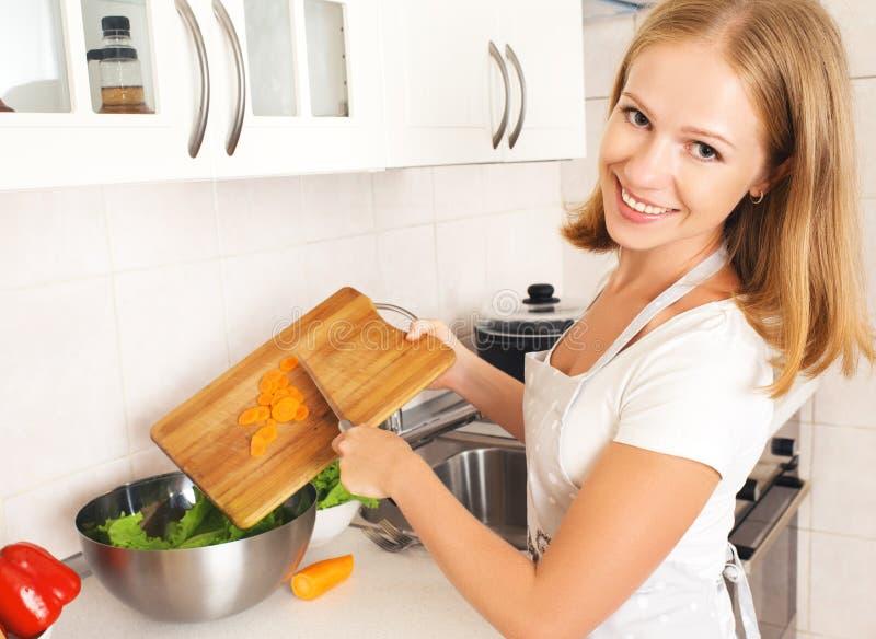 准备沙拉的愉快的妇女主妇在厨房里 免版税库存照片