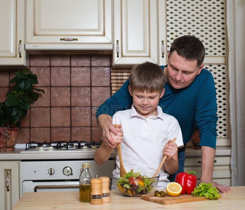 准备沙拉的愉快的父亲和他的儿子画象在厨房里 库存图片