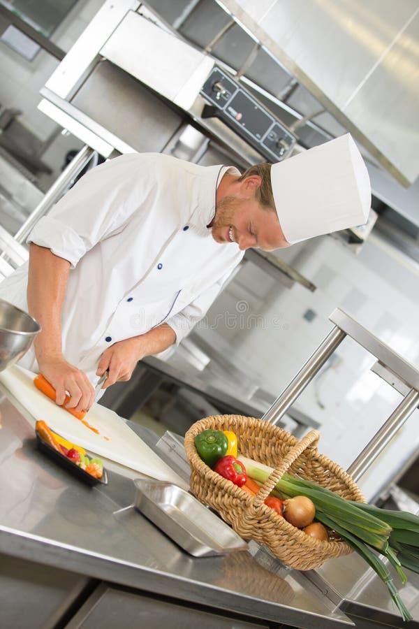 准备沙拉的英俊的厨师在餐馆厨房里 库存照片