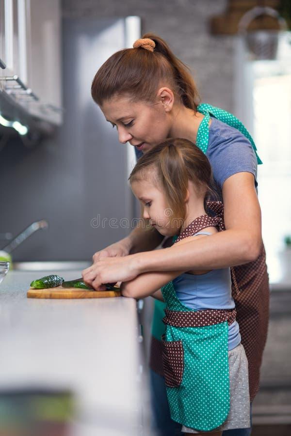 准备沙拉膳食的母亲和女儿在厨房里 库存图片