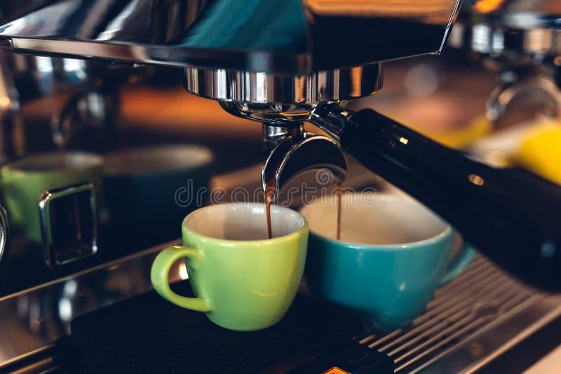 准备浓咖啡和涌入色的杯子的咖啡机器 免版税图库摄影