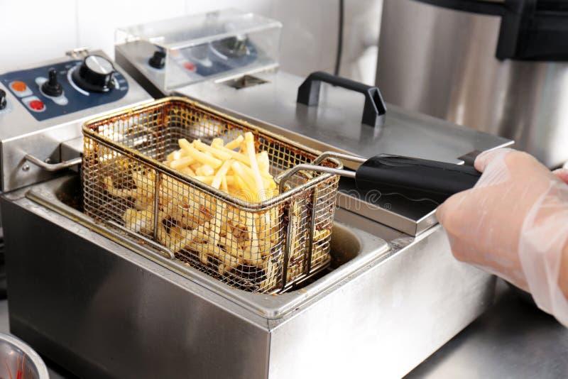 准备炸薯条的女性厨师 免版税库存照片