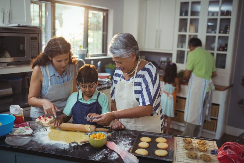 准备点心的家庭在厨房里 图库摄影