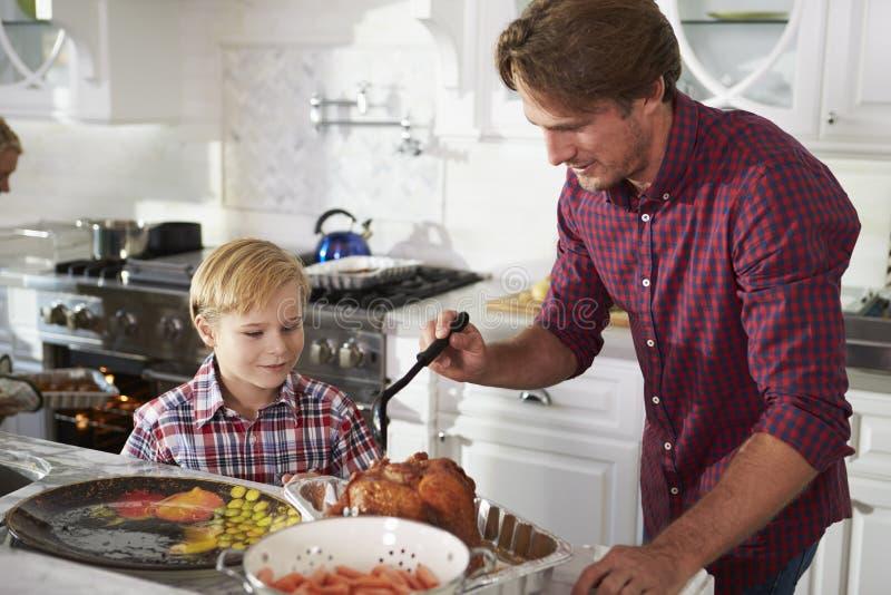 准备烘烤土耳其膳食的父亲和儿子在厨房里 库存照片