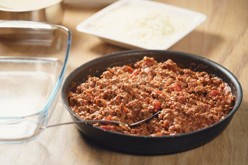 准备烤宽面条过程用在平底锅的博洛涅塞调味汁 免版税库存照片