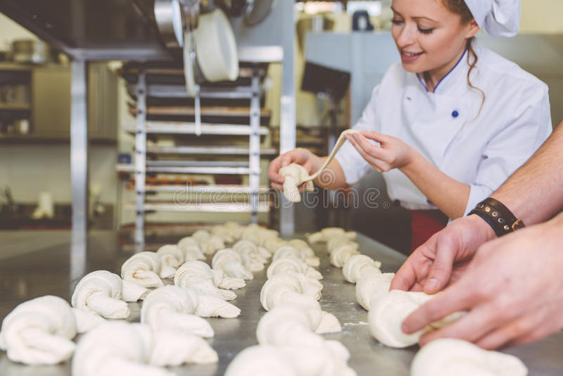 准备甜新月形面包的厨师在面包点心店实验室 免版税库存照片