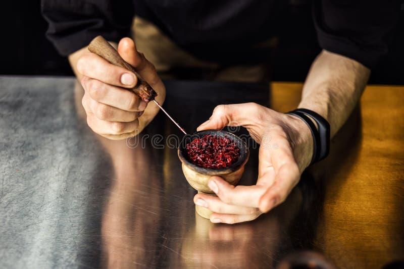 准备由男服务员的Shisha水烟筒 侍酒者放置sm的烟草 免版税库存图片