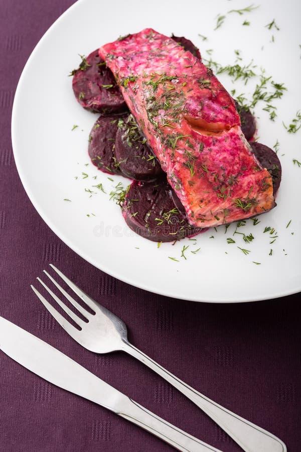 准备的三文鱼内圆角用甜菜和调味汁在白色板材 免版税图库摄影