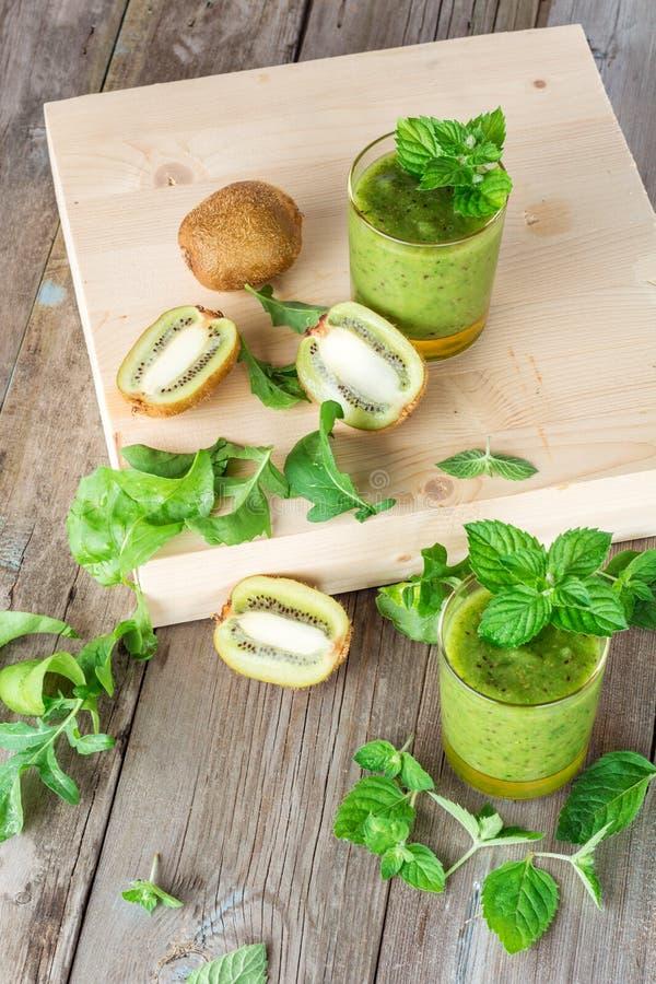 准备的成份:猕猴桃、芝麻菜、薄菏和两名玻璃圆滑的人 库存图片