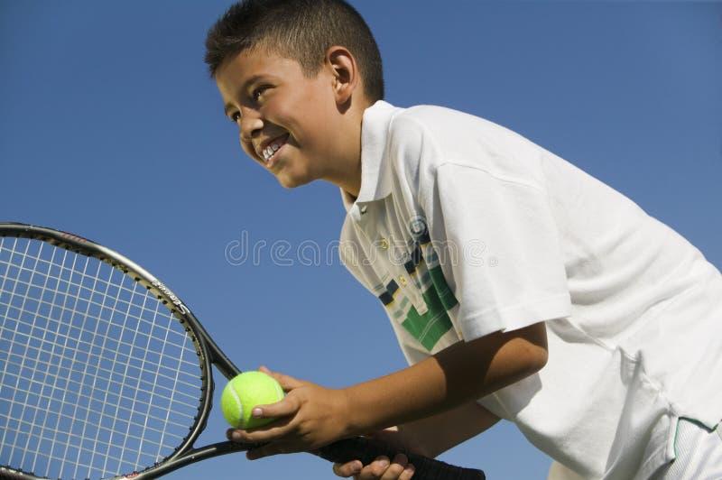 准备的网球场的年轻男孩服务紧密低角度视图 库存照片