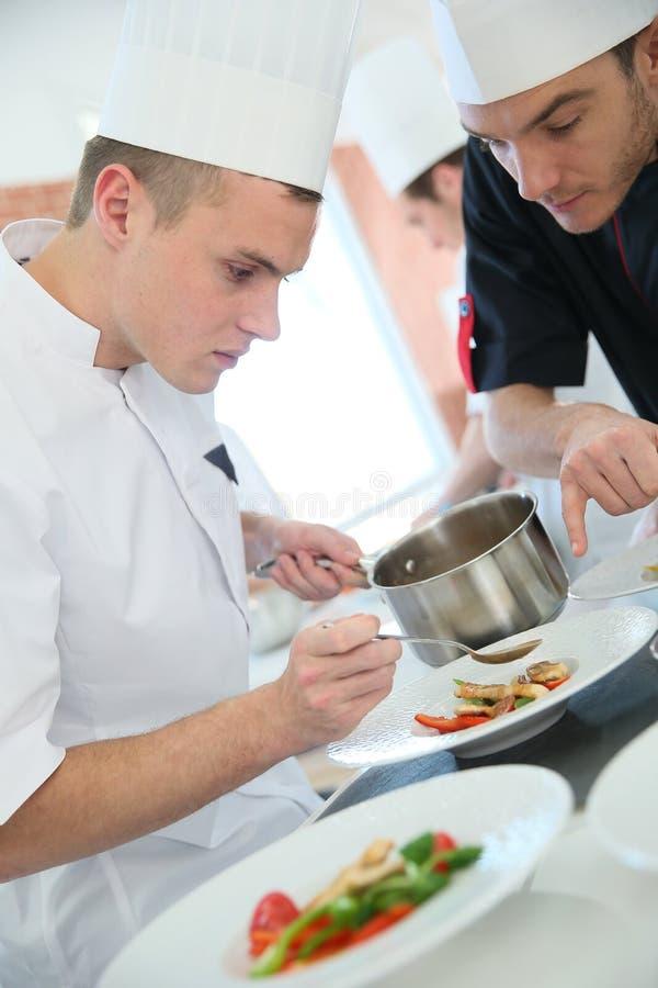 准备盘的年轻烹调厨师 免版税库存照片
