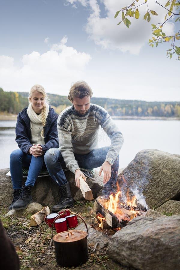 准备篝火的夫妇在湖边野营期间 库存照片