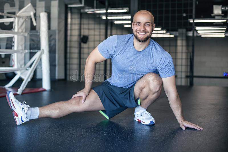 准备肌肉的坚强的运动员在训练前 做行使在健身房的肌肉运动员 男性舒展 专业sportsma 免版税图库摄影