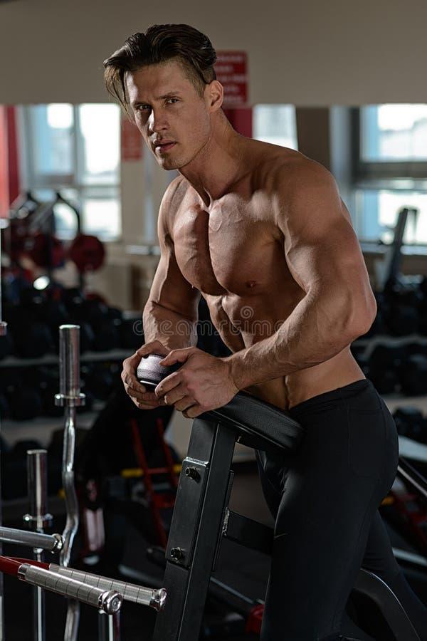准备肌肉的爱好健美者行使在健身房 免版税库存照片