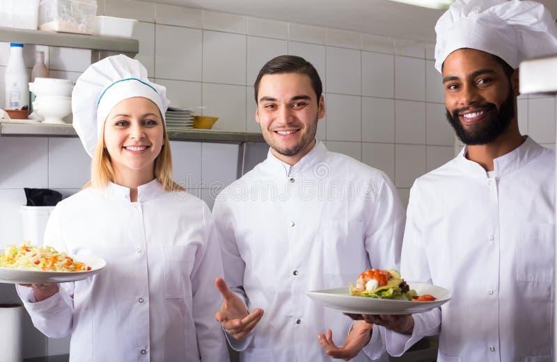准备膳食的厨师和他的助理 图库摄影
