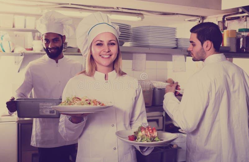 准备膳食的厨师和他的助理 库存照片