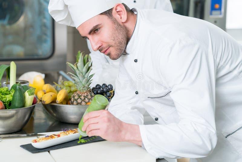 准备膳食的年轻厨师在厨房里 库存图片