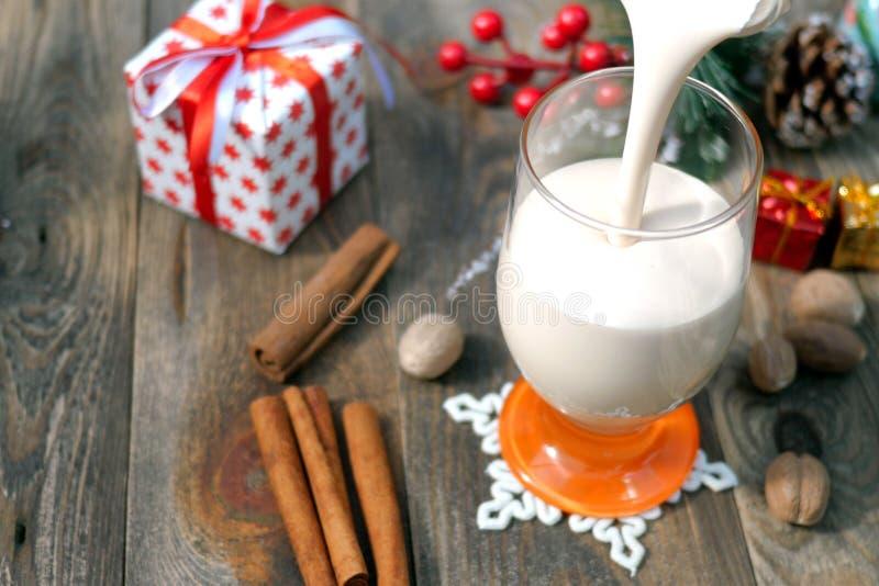 准备自创传统圣诞节辣热的饮料蛋黄乳用碎肉豆蔻,在一块玻璃的桂香,滑稽的圣诞节的 免版税库存图片