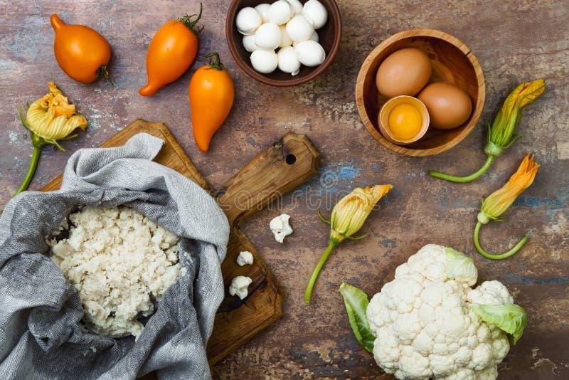 准备花椰菜薄饼用硬皮覆盖与pesto、黄色蕃茄、夏南瓜、无盐干酪乳酪和南瓜开花 库存图片