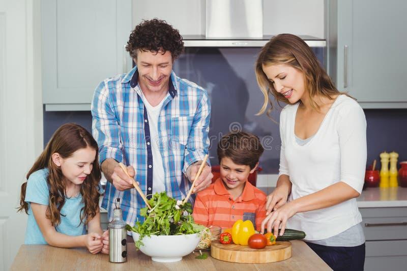 准备菜沙拉的父母和孩子 免版税库存照片