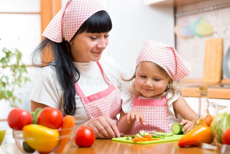 准备菜的妇女和孩子女儿在厨房 图库摄影