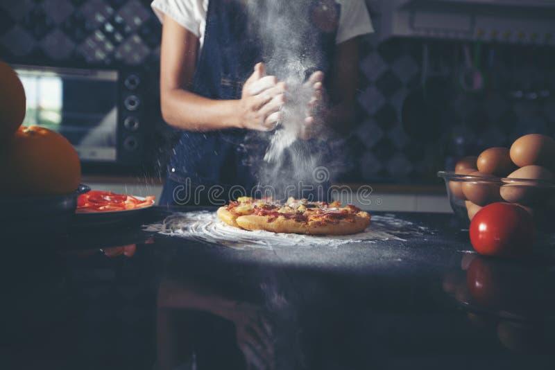 准备薄饼的亚裔妇女,揉面团并且投入ingredie 库存照片