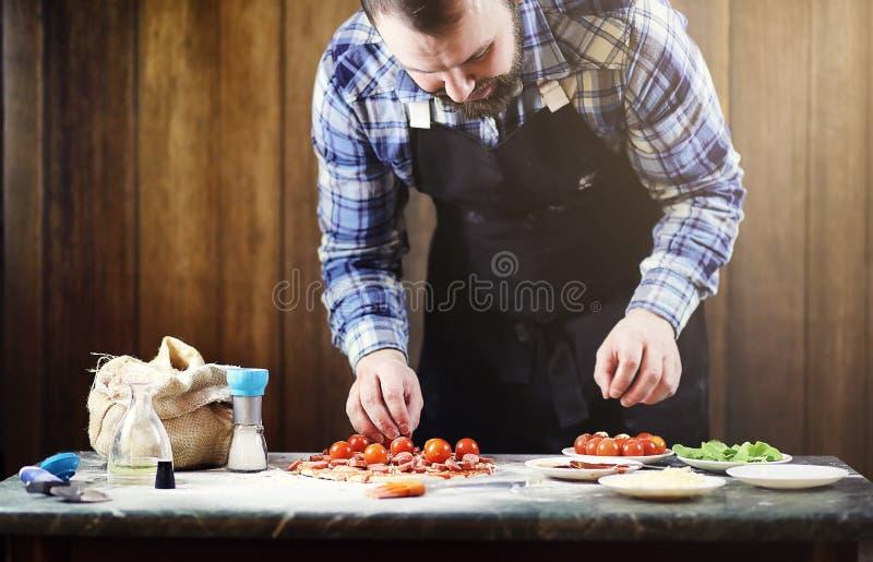 准备薄饼的围裙的人,揉面团并且投入ingr 库存图片