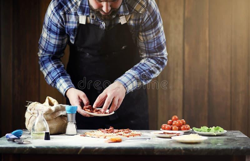 准备薄饼的围裙的人,揉面团并且投入ingr 免版税库存图片