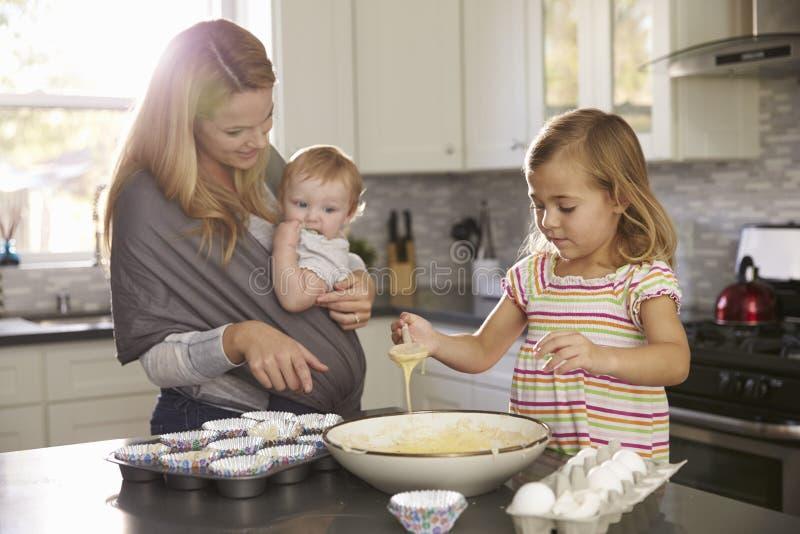 准备蛋糕粉的女孩在厨房,显示婴孩的妈咪里 免版税图库摄影