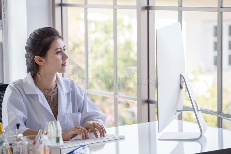 准备试管和分析有计算机的年轻亚裔妇女研究科学家显微镜在实验室 免版税库存图片