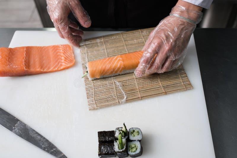 准备费城寿司卷的厨师三文鱼 免版税库存照片