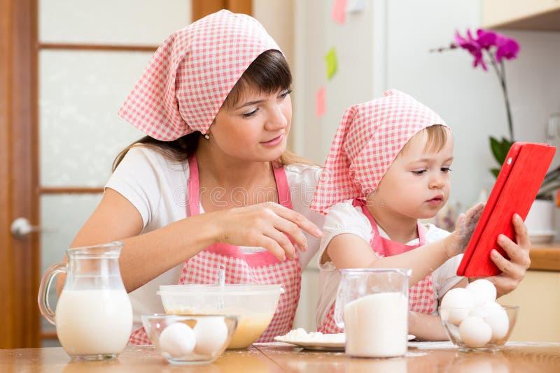 准备酥皮点心的母亲和孩子看菜谱 图库摄影