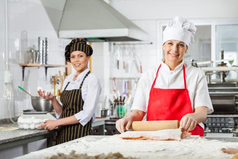 准备面团的愉快的女性厨师在厨房里 库存照片