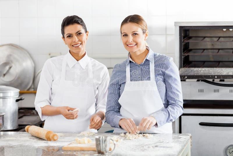 准备面团的愉快的女性厨师在柜台 免版税库存图片