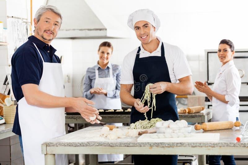 准备面团的愉快的男性和女性厨师在 库存照片