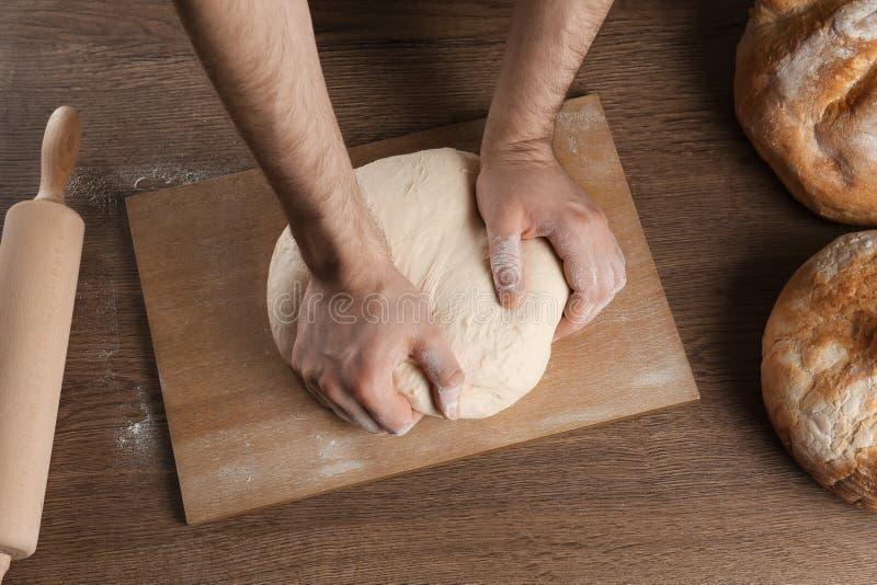 准备面团的男性面包师在木桌上 免版税库存照片