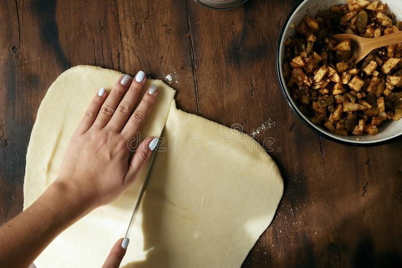 准备面团苹果果馅奶酪卷顶视图的妇女 免版税库存图片