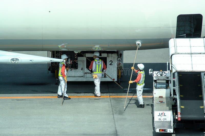 准备飞机的工作者对飞行 在登巴萨机场  免版税库存图片