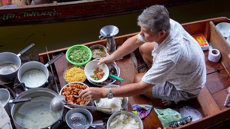准备食物的人在Damnoen Saduak浮动市场上在Bangko附近 免版税库存图片