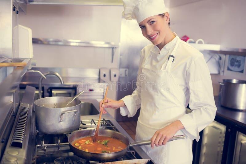 准备食物的女性厨师在厨房里 免版税库存照片