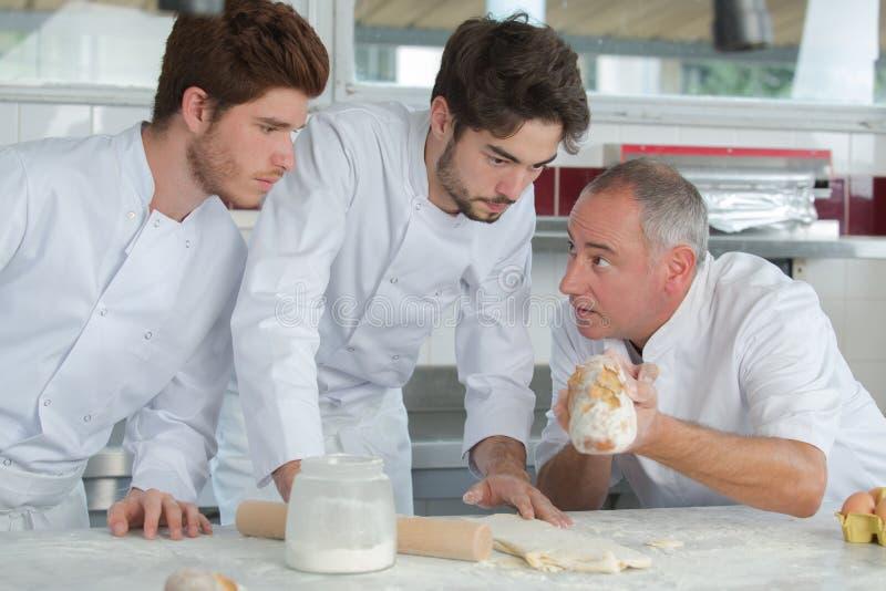 准备食物的年轻厨师在厨房里在餐馆 图库摄影