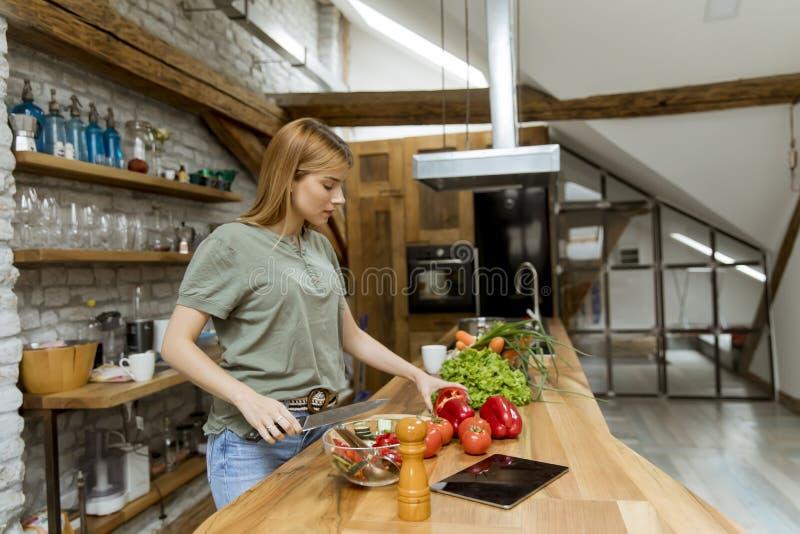 准备食物的年轻女人在土气厨房里 免版税库存照片