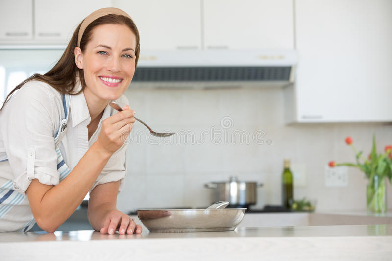准备食物的微笑的少妇在厨房里 库存图片