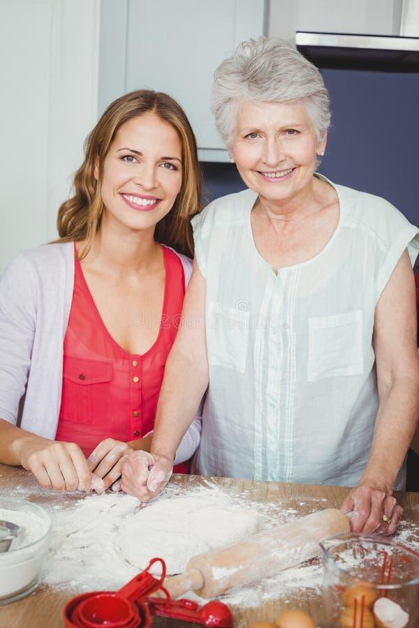 准备食物的母亲和女儿画象  免版税库存图片
