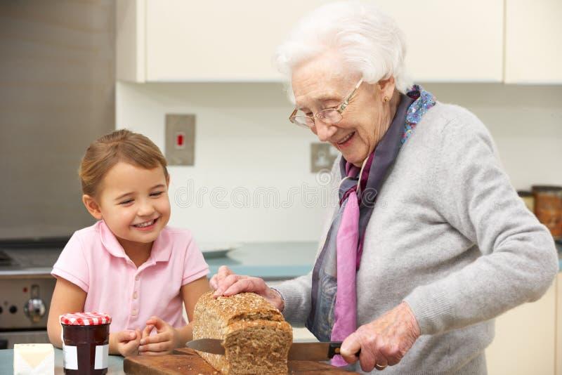 准备食物的祖母和孙女 库存图片